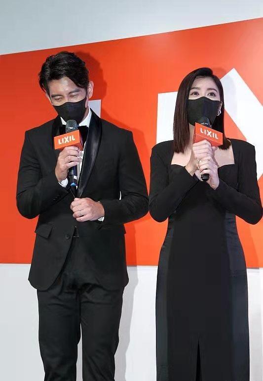 Vợ chồng Giả Tịnh Văn tham dự sự kiện, cô diện váy bó sát, không có vết sần trên cơ thể, có phần dịu dàng hơn chồng.